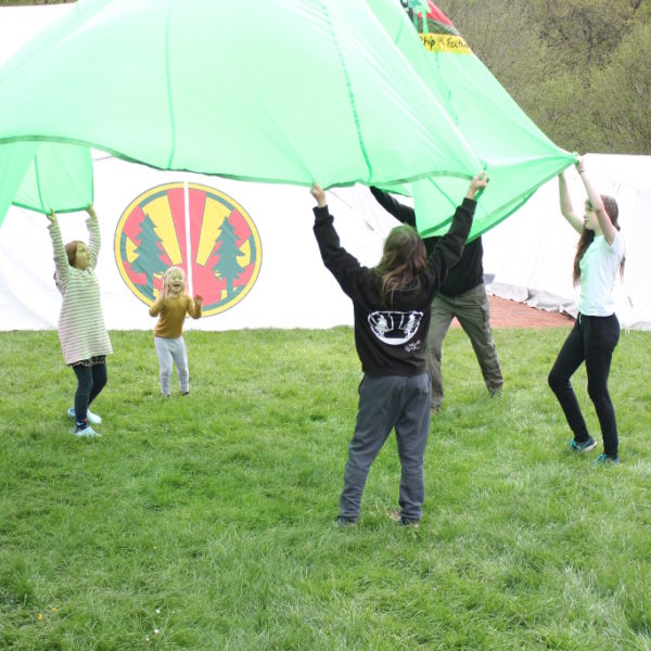Children playing parachute games in front of the marquee
