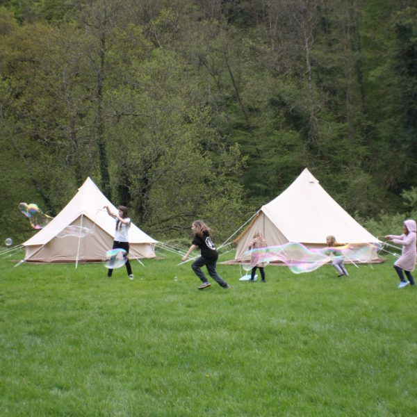 Children chasing bubbles in fron of tents