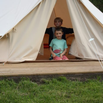 Two children looking out of a Bell Tent.