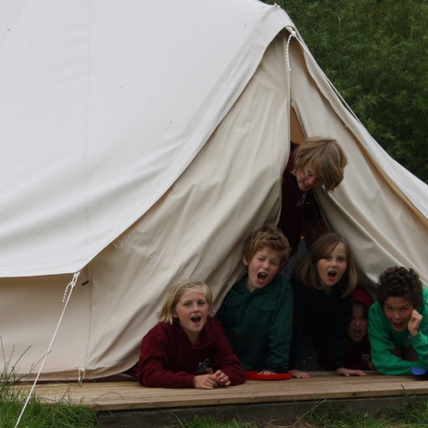 Children looking out from a bell tent