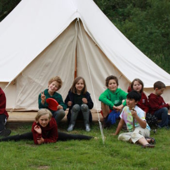 Children sitting outside a bell tent