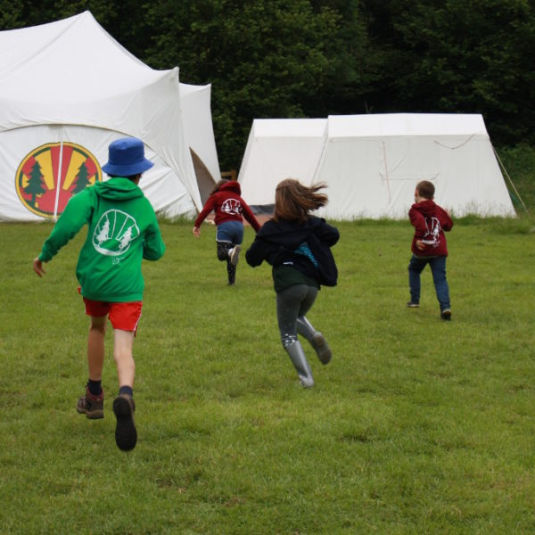 Children running towards a marquee