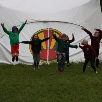 Children jumping outside a marquee