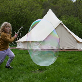 Child chasing a ginat bubble outside a tent