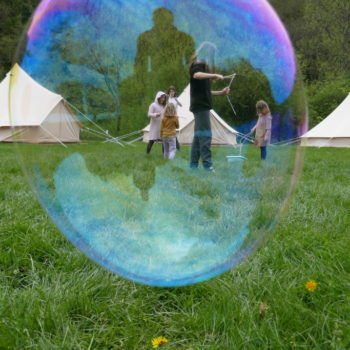 Looking through a bibble at a group of children playing in front of a row of tents.