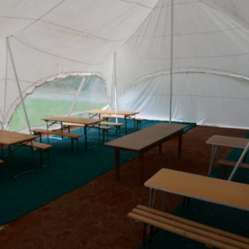 Tables and benches inside the camp Kudoo marquee