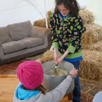Children mashing a large pan of potatoes