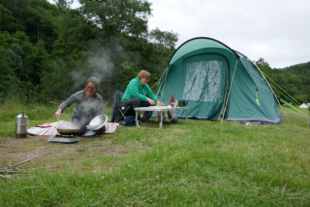Family cooking outside thier tent.